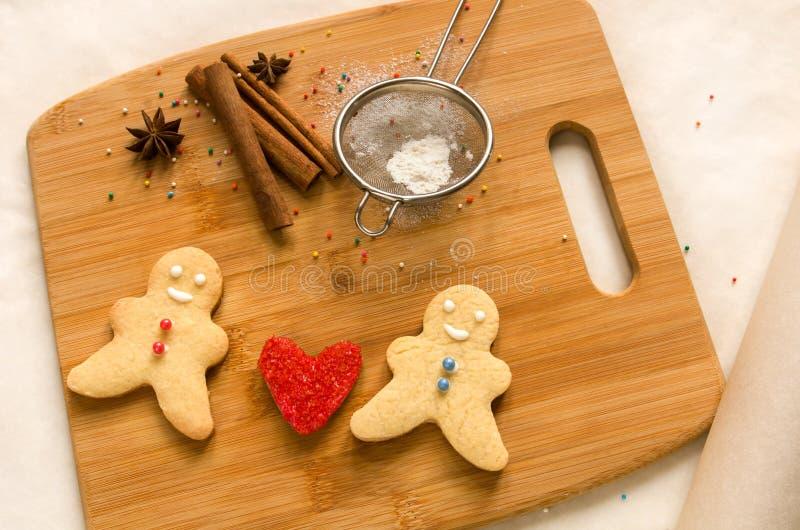 曲奇饼人和面团的心脏在一个木板的 爱的概念 免版税库存照片