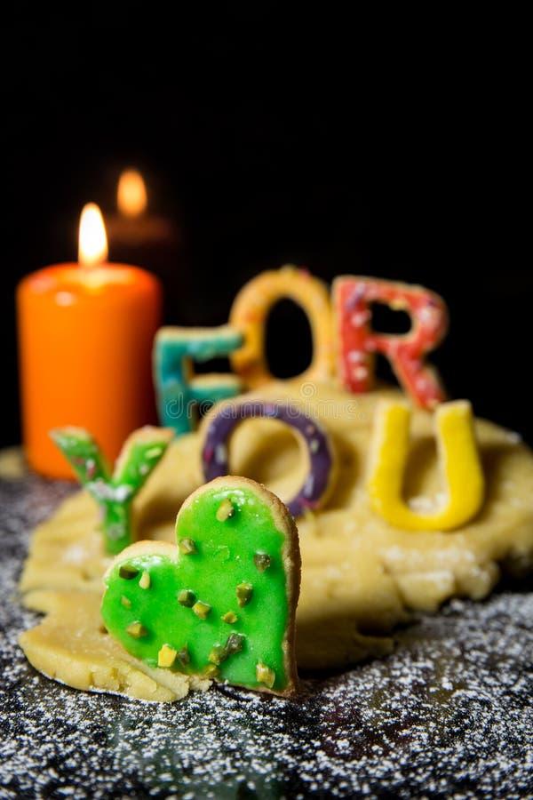 曲奇饼信件用曲奇饼面团和一个蜡烛,您的文本f的 图库摄影
