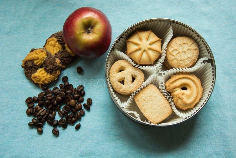 曲奇饼用在一个圆的箱子,两说谎在一张桌布的与咖啡豆和一个苹果的糖 库存图片