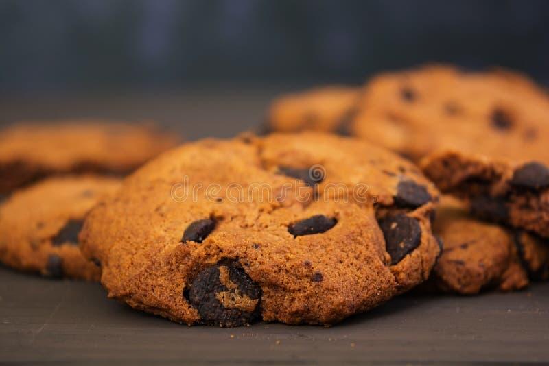 曲奇饼用在黑暗的木背景的巧克力 图库摄影