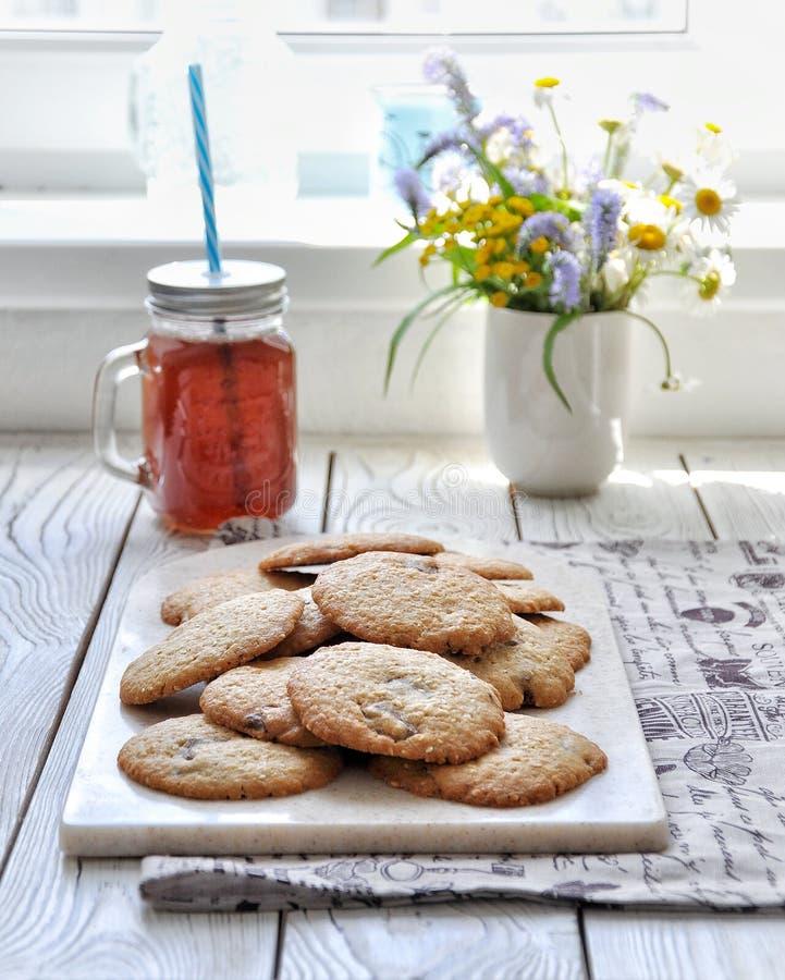 曲奇饼用芝麻和牛奶巧克力 玻璃圆滑的人 水果鸡尾酒的玻璃瓶子 免版税库存照片