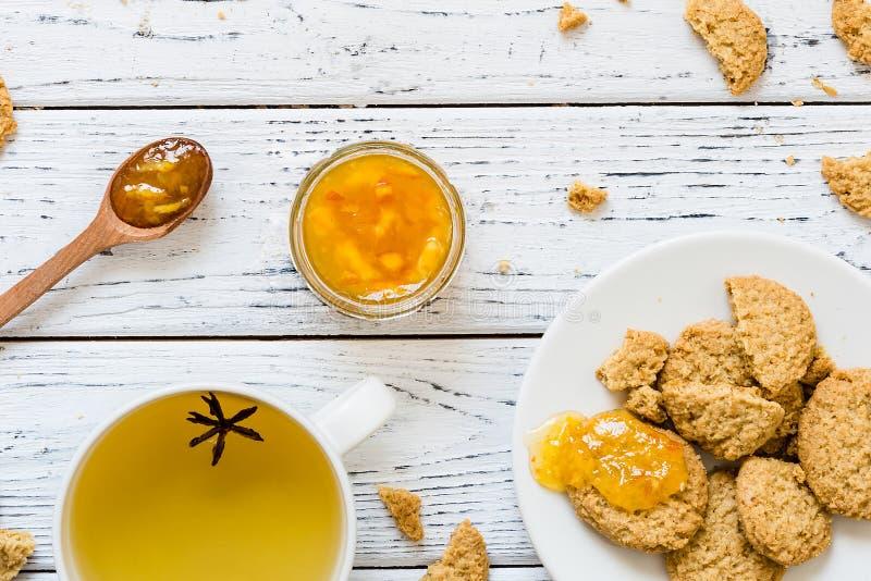 曲奇饼,橙色果酱,茶用在白色木背景的茴香 免版税库存图片