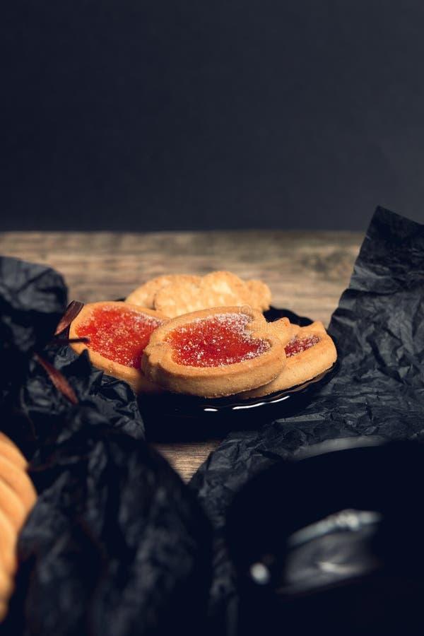 曲奇饼,饼干充满红草莓在黑桌背景阻塞 顶视图,拷贝空间 库存照片