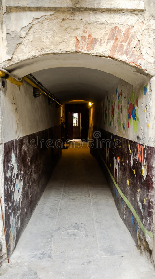 以曲拱的形式走廊在一个老房子的老门廊有一个门的在与电灯泡出口的黑暗在利沃夫州 免版税库存图片