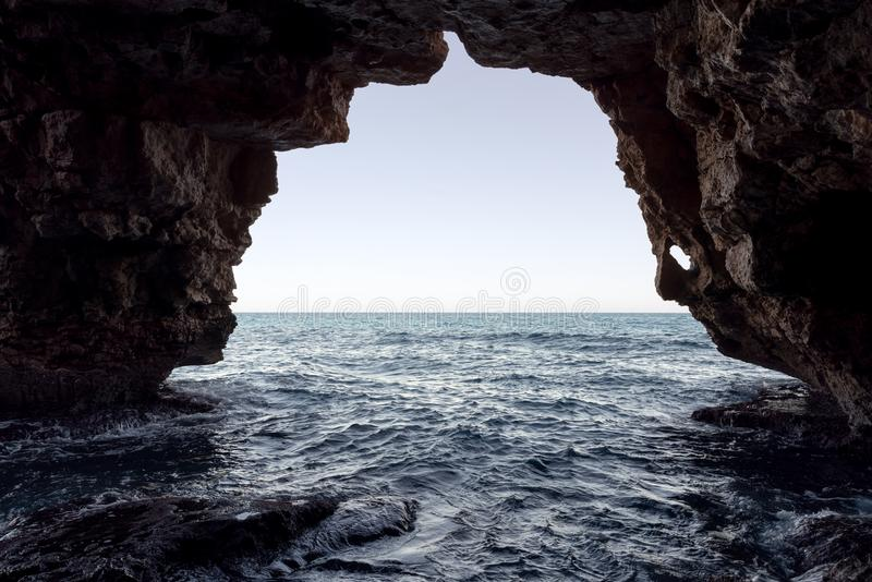 曲拱的洞在Moraig小海湾的  库存图片