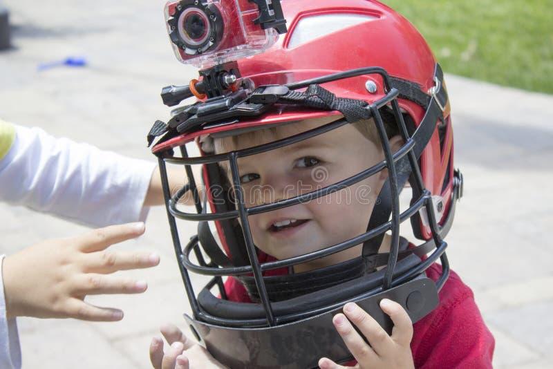 头戴曲棍网兜球盔甲的小男孩 免版税库存照片