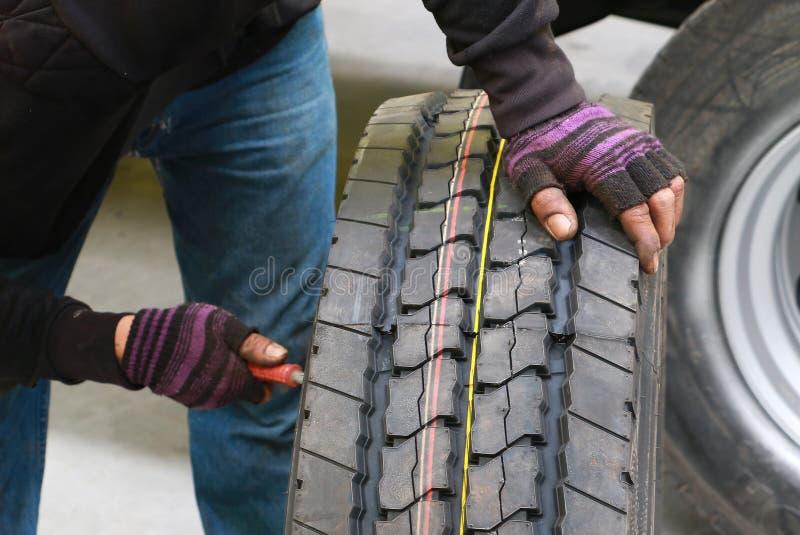 更换一辆汽车卡车的轮子的亚裔人技工在车间 技工改变的卡车把汽车修理店引入 免版税库存照片