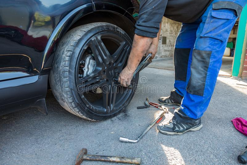 更换在汽车的人一个轮子 库存图片