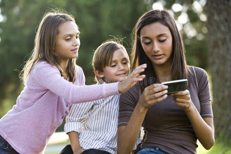 更新女孩兄弟青少年的texting的手表 库存图片