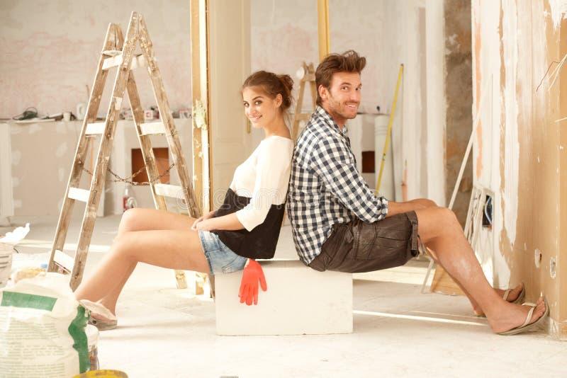 更新愉快的夫妇在家 免版税库存照片