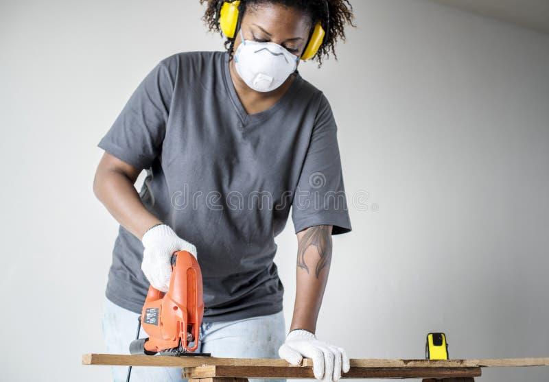 更新房子DIY概念的年轻非洲妇女 库存照片