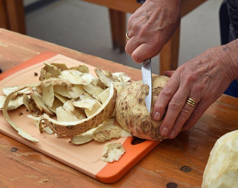 更旧的女性手切了与一把厨刀的芹菜在木t 免版税库存图片