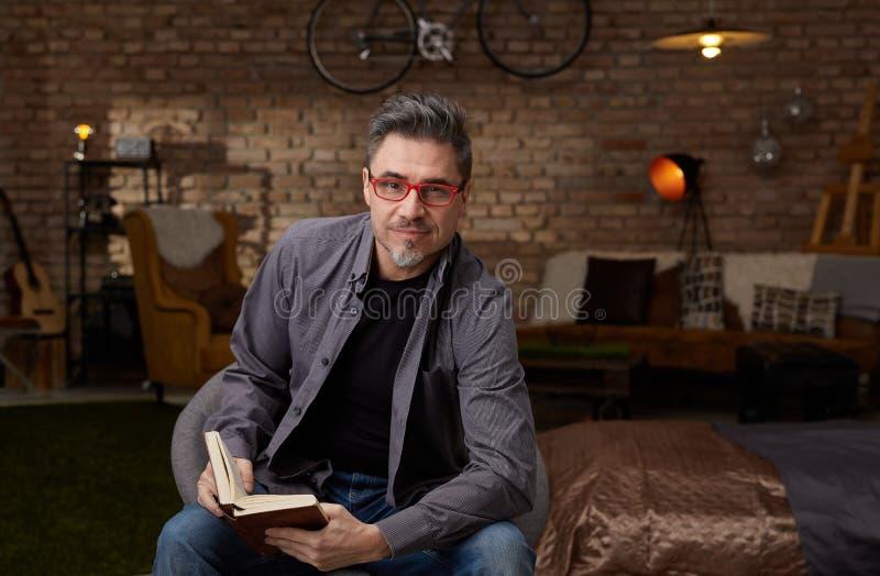 更旧的白人阅读书在家 免版税图库摄影