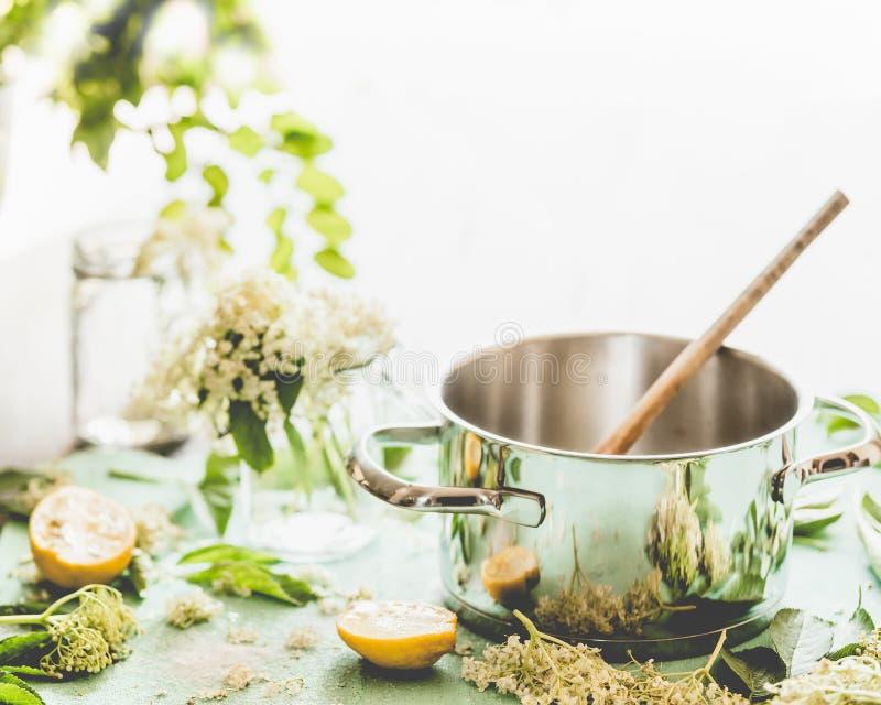 更旧的花糖浆或果酱准备 有匙子、Elderflowers和柠檬的罐在厨房用桌上 免版税库存照片