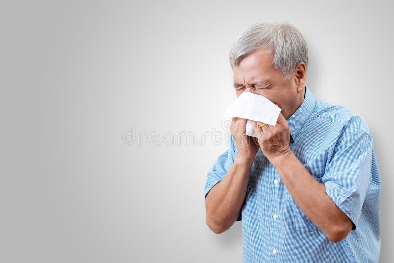 更老的亚裔人有流感并且打喷嚏从憔悴季节性病毒问题 免版税库存图片