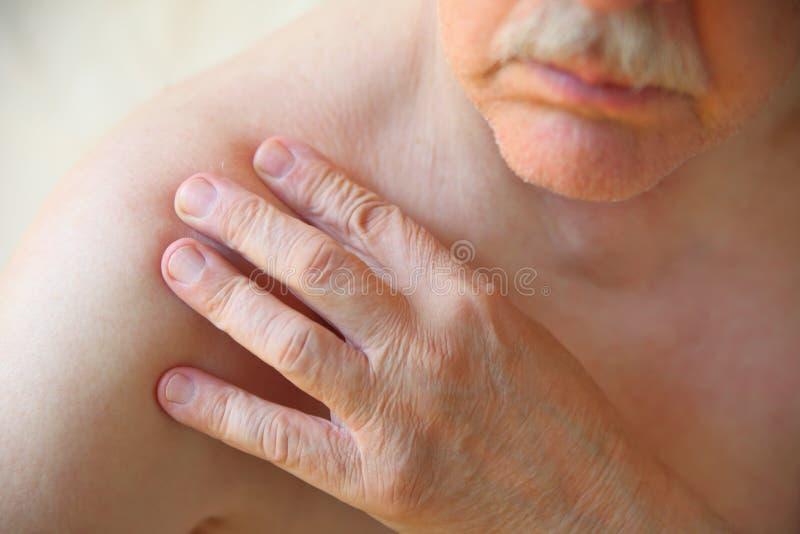 更老的人有疼痛在肩膀 免版税库存照片