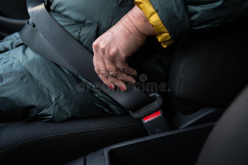 更老的资深妇女紧固在穿绿色和救生服的汽车的一个安全带 免版税库存图片