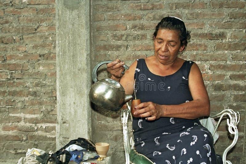 更老的阿根廷妇女倾吐伙伴茶的水 库存图片