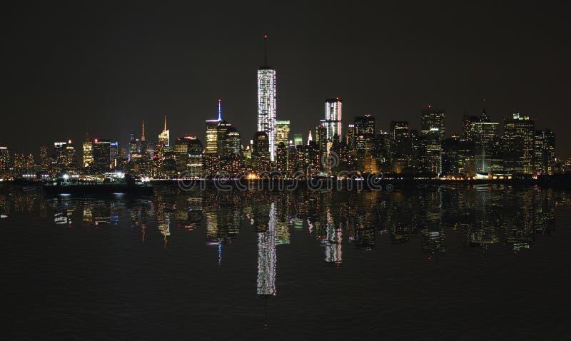曼哈顿在晚上,与反射的纽约地平线 免版税图库摄影