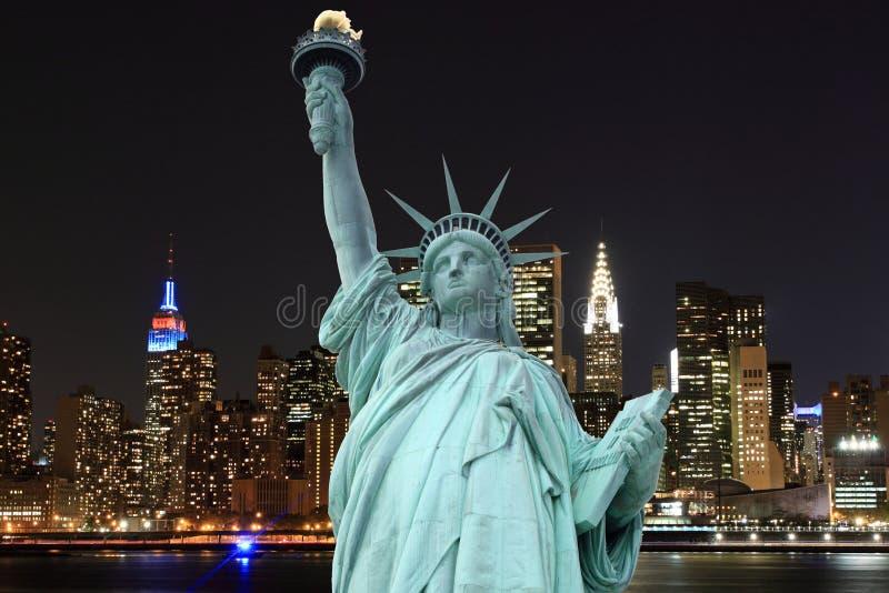 曼哈顿地平线和自由女神象在晚上 库存照片