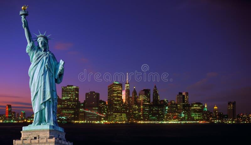 曼哈顿地平线在夜和自由女神像里 免版税库存照片
