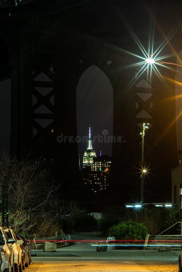 曼哈顿大桥和曼哈顿的看法从East河的河沿在晚上与帝国大厦在 图库摄影