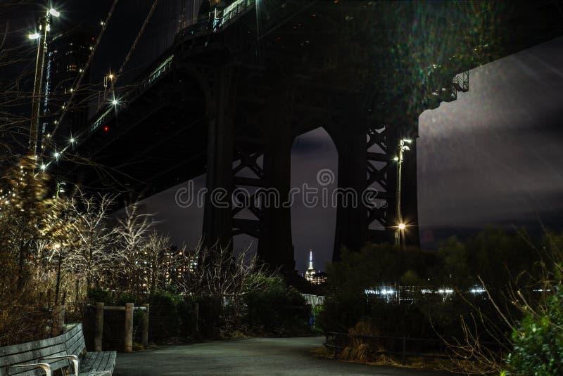 曼哈顿大桥和曼哈顿的看法从East河的河沿在晚上与帝国大厦在 库存照片