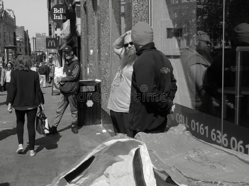 曼彻斯特街曼彻斯特晚间新闻人供营商在商店窗口里反射了 免版税库存照片