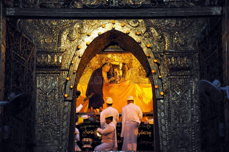 曼德勒,缅甸10月9日:对菩萨的资深修士浪花水在面孔洗涤仪式面对给菩萨 免版税库存照片