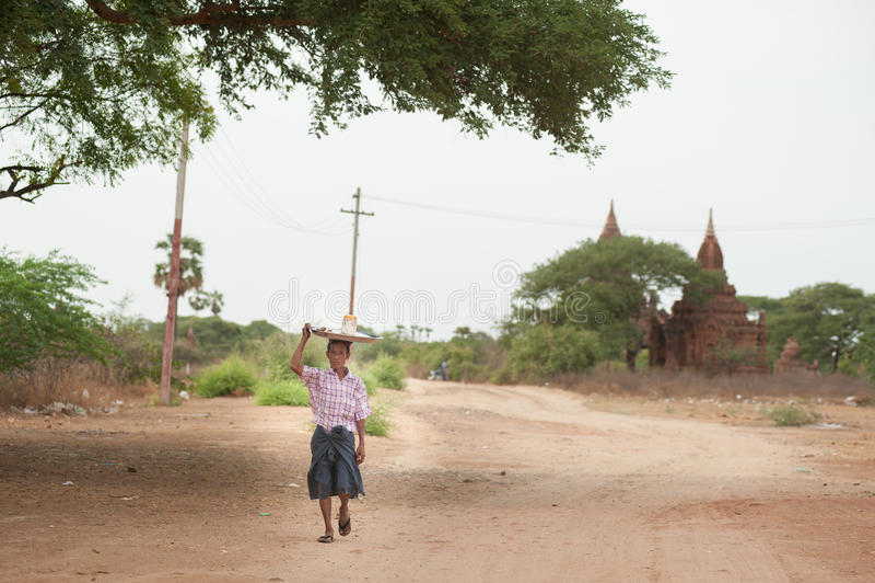 曼德勒,缅甸- 5月3 : 一个人运载一个袋子他朝向, 库存照片