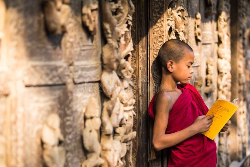 曼德勒, MYANMAR-FEB 18 :读年轻新手的修士站立和 免版税库存照片