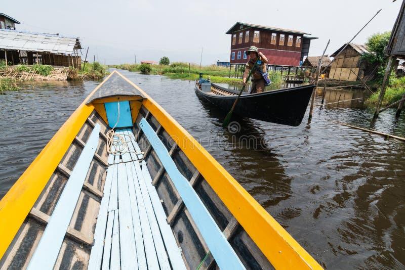 曼村Thauk,缅甸- 2019年4月:努力去做通过曼村Thauk村庄的传统缅甸木小船在Inle湖 库存图片