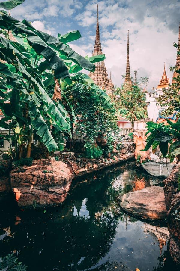 曼谷全部宫殿 曼谷大皇宫伸手可及的距离塔到天空里 一点在寺庙里面的湖 免版税图库摄影