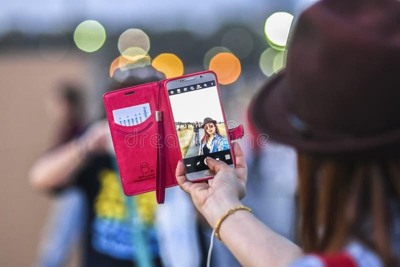 曼谷,泰国, 2016年3月4日:做selfie的少妇由她的电话,有bokeh的在背景中 库存照片