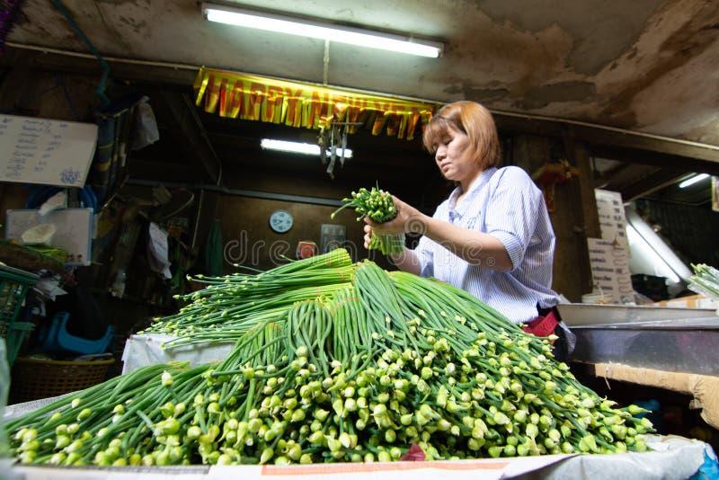 曼谷,泰国- 2019年3月:卖绿叶和菜的妇女在市场上 库存照片