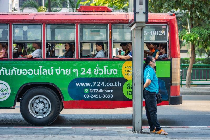 曼谷,泰国- 2018年11月:在倾斜反对杆,有人的一辆红色公共汽车的街道上的妇女身分在b的奔跑里面 库存图片