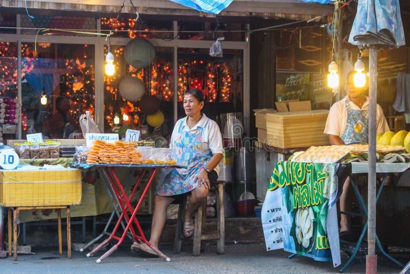 曼谷,泰国- 2017年10月:摊贩泰国妇女在卖她的手工制造甜点和物品的Chatuchak市场上 库存照片