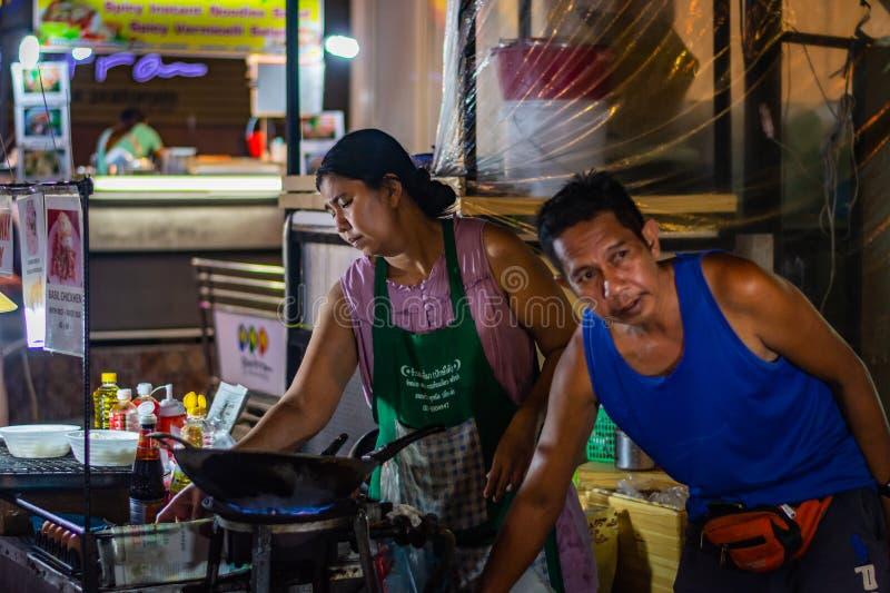 曼谷,泰国- 2018年11月:泰国回教夫妇是准备和烹调泰国食物在夜市的晚上 库存图片