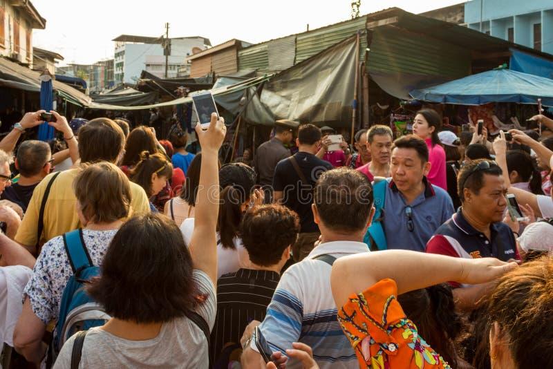 曼谷,泰国- 2018年1月27日:为火车照相的游人在Maeklong铁轨市场(火车市场)上 库存照片