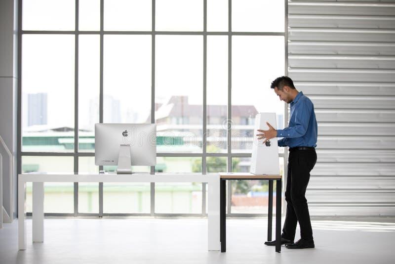 曼谷,泰国- 2018年5月05日:亚洲年轻商人在办公室箱中取出并且设定了两台新的iMac计算机 苹果电脑 免版税库存图片