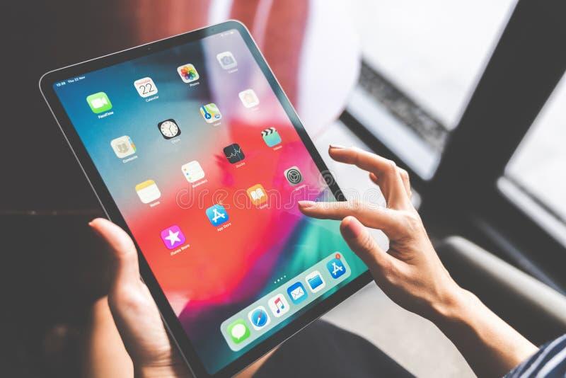 曼谷,泰国- 2018年11月22日:使用新的11英寸苹果计算机iPad的亚裔妇女赞成2018年,猛击家庭屏幕或接触应用程序象 免版税库存图片