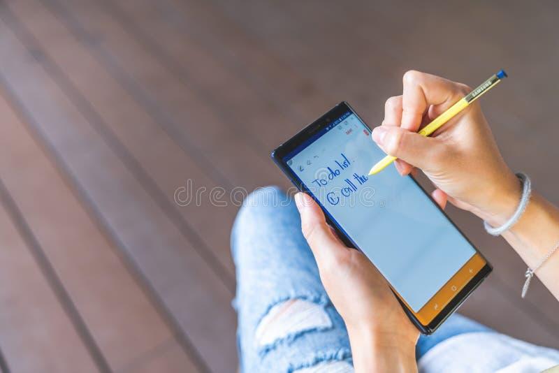 曼谷,泰国- 2018年8月28日:使用黄色S笔铁笔的亚洲妇女手在三星星系笔记9屏幕上,写提示 库存照片