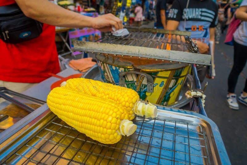曼谷,泰国- 2018年3月21日:关闭两在格栅的玉米棒子,准备好被烤在街道  免版税库存照片