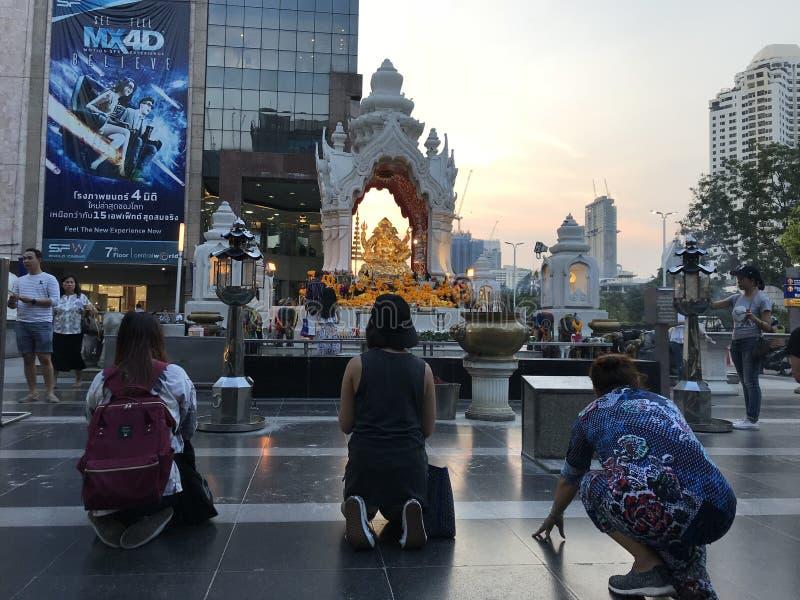 曼谷,泰国- 2018年4月16日:宗教人民在buddist寺庙附近在市中心祈祷与的摩天大楼 免版税库存图片
