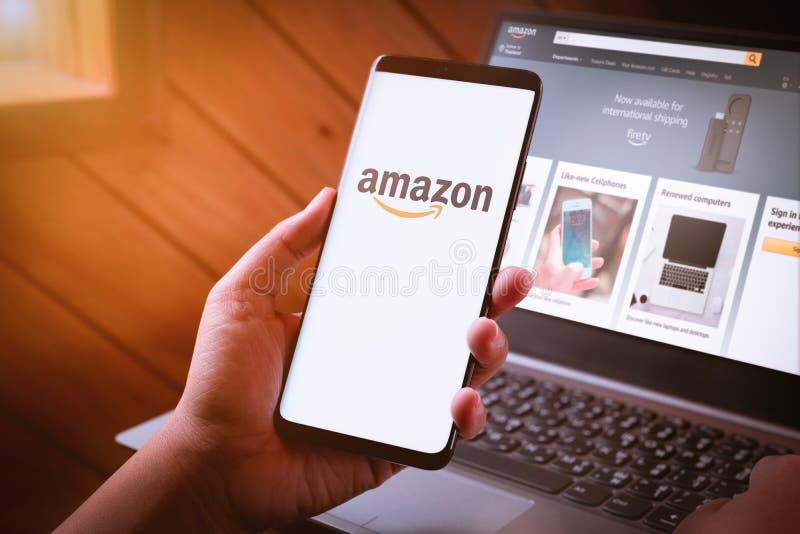 曼谷,泰国- 2019年8月5日:拿着有亚马逊商标的妇女手智能手机在屏幕和亚马逊网站上膝上型计算机的 库存照片