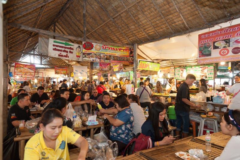 曼谷,泰国- 2018年2月11日:游人喜欢购物和吃泰国街道食物在小伙子Mayom浮动市场上 图库摄影