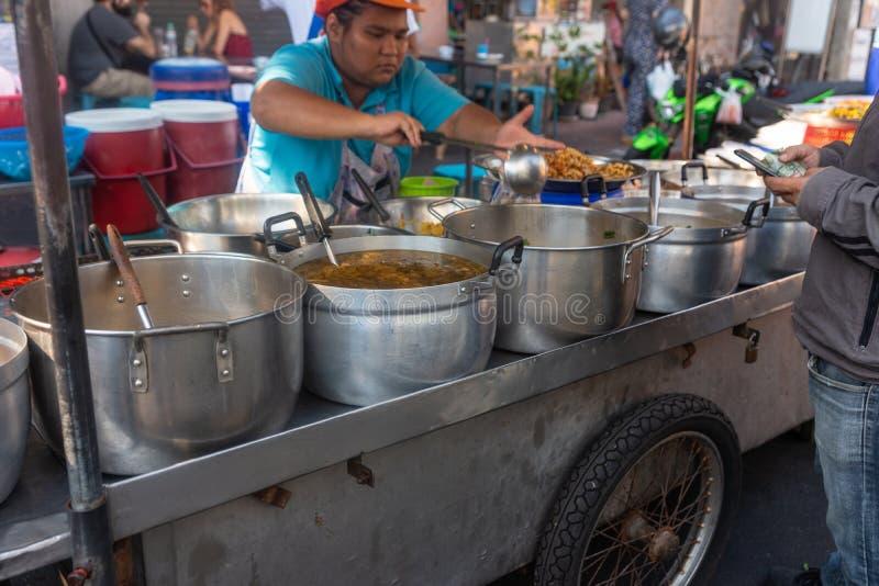 曼谷,泰国- 2019年2月14日:烹调在巨大的平底锅的人猪肉使用在天街道食物市场上的杓子 库存照片