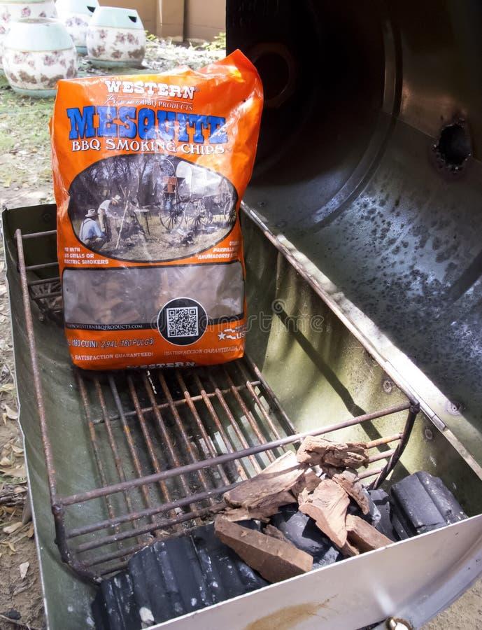 曼谷,泰国- 2018年5月12日:西部豆科灌木BBQ抽烟的芯片和木炭在便携式的烤肉在后院烤 图库摄影