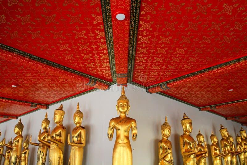 曼谷,泰国- 2016年2月19日:许多站立与红色天花板和白色墙壁的金黄菩萨雕象在Arunratchawararam Tem 库存图片