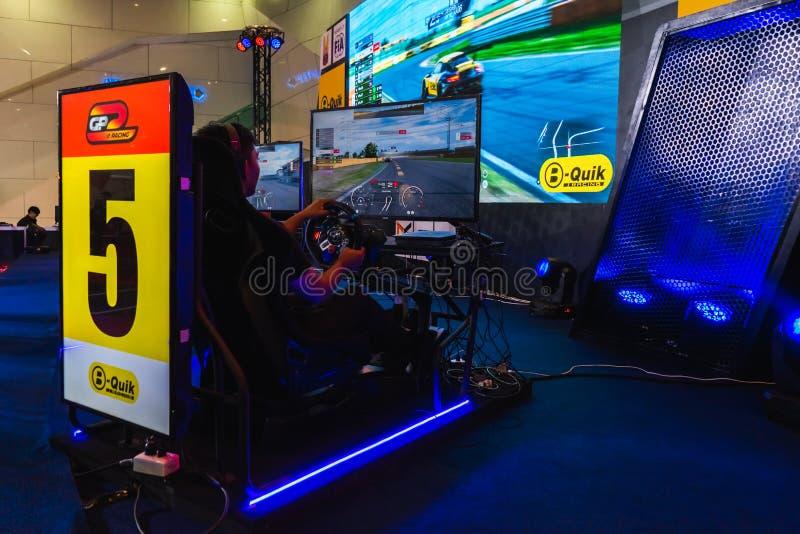曼谷,泰国- 2019年3月31日:驾驶有现实屏幕E体育技术比赛GP e赛跑的比赛的游戏玩家模仿汽车在 图库摄影
